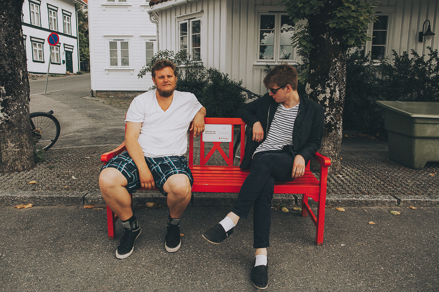 Two boys sitting on a red bench