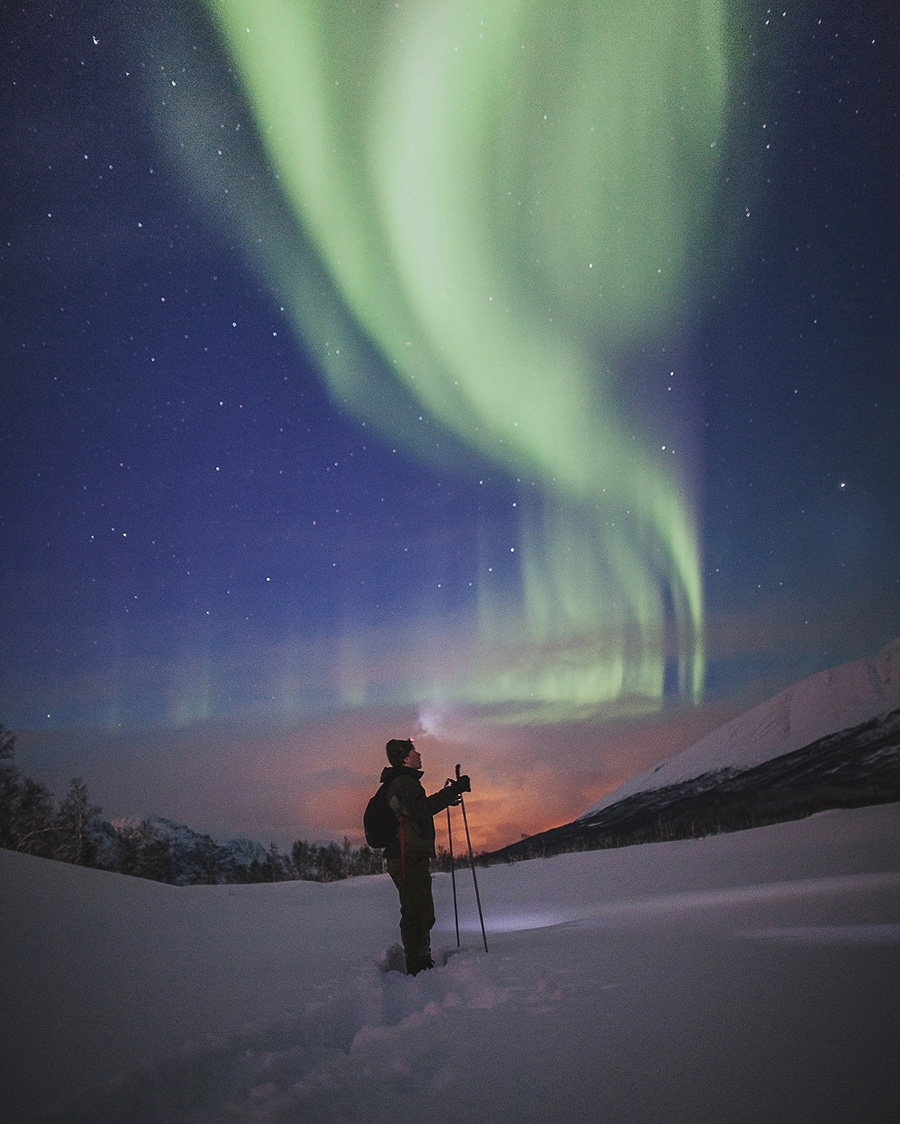 Man looking up at he northern lights dancing