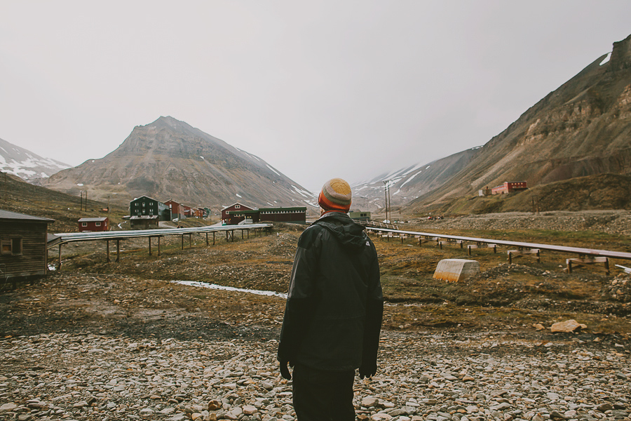 Man looking at Nybyen in Svalbard