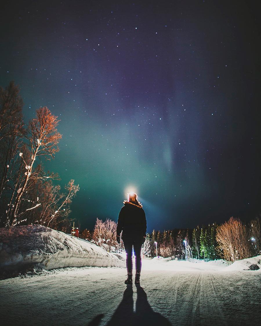 Girl looking at northern lights in Tromsø