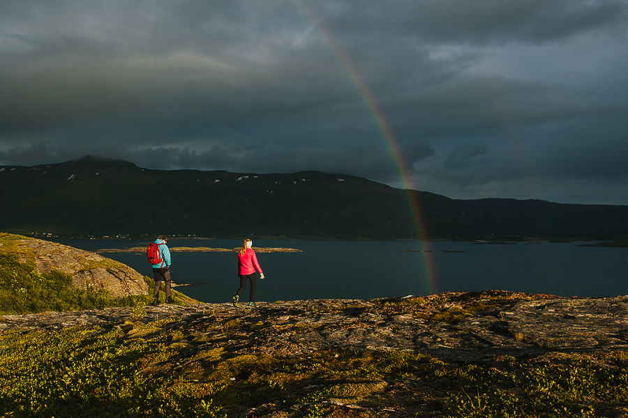 Girl and boy walking under the rainbow