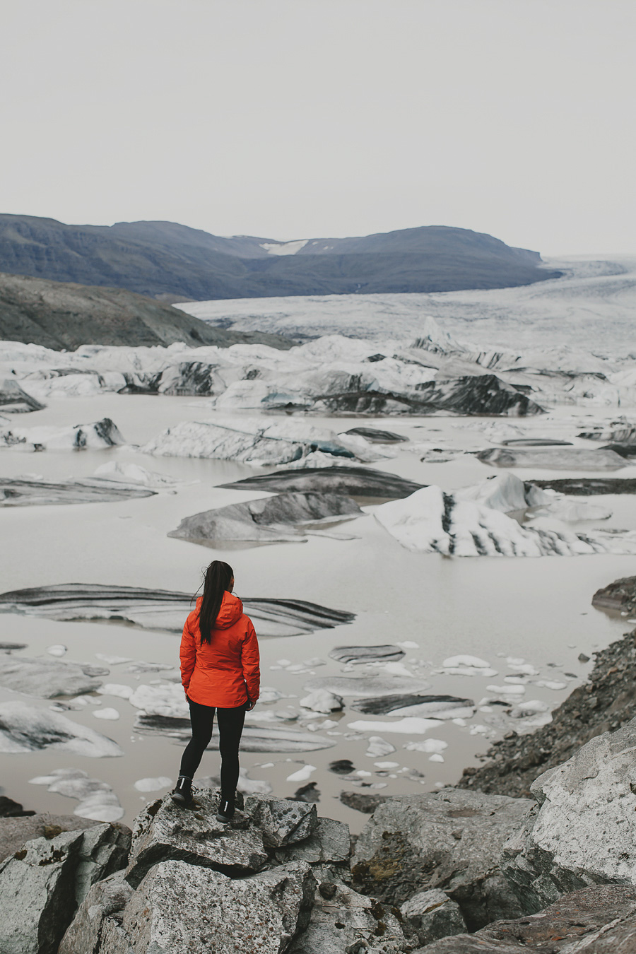 Girl dressed in red in front of a glacier in Iceland