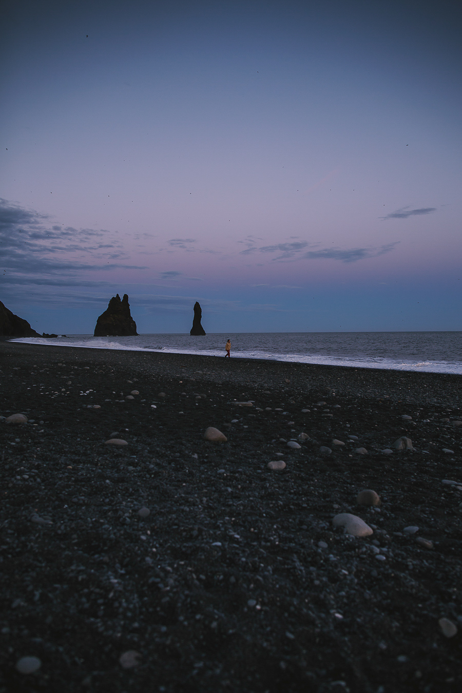 Girl in yellow walking on a black beach in Iceland