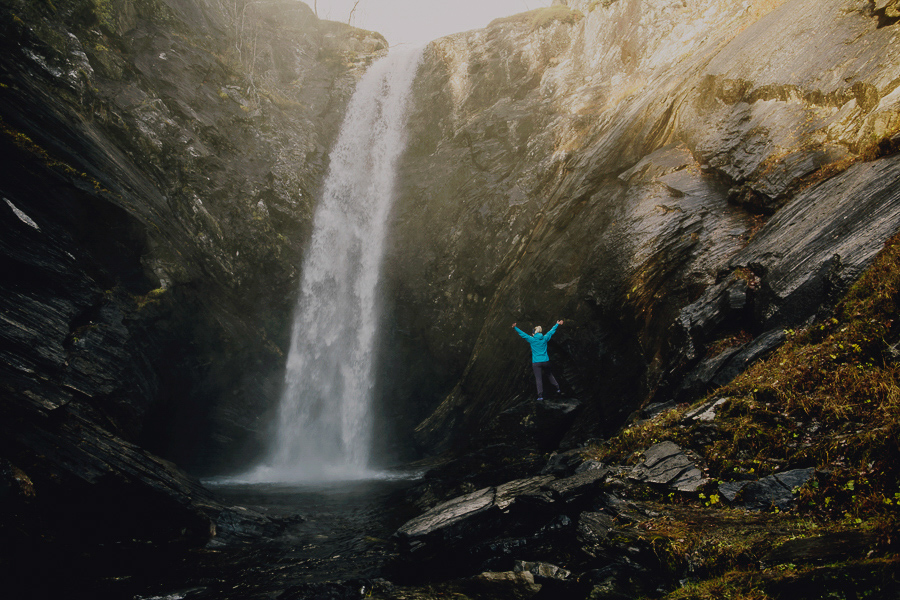 Girl in a blue jacket with a waterfall