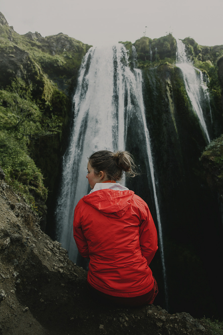 Girl sitting by a waterfall