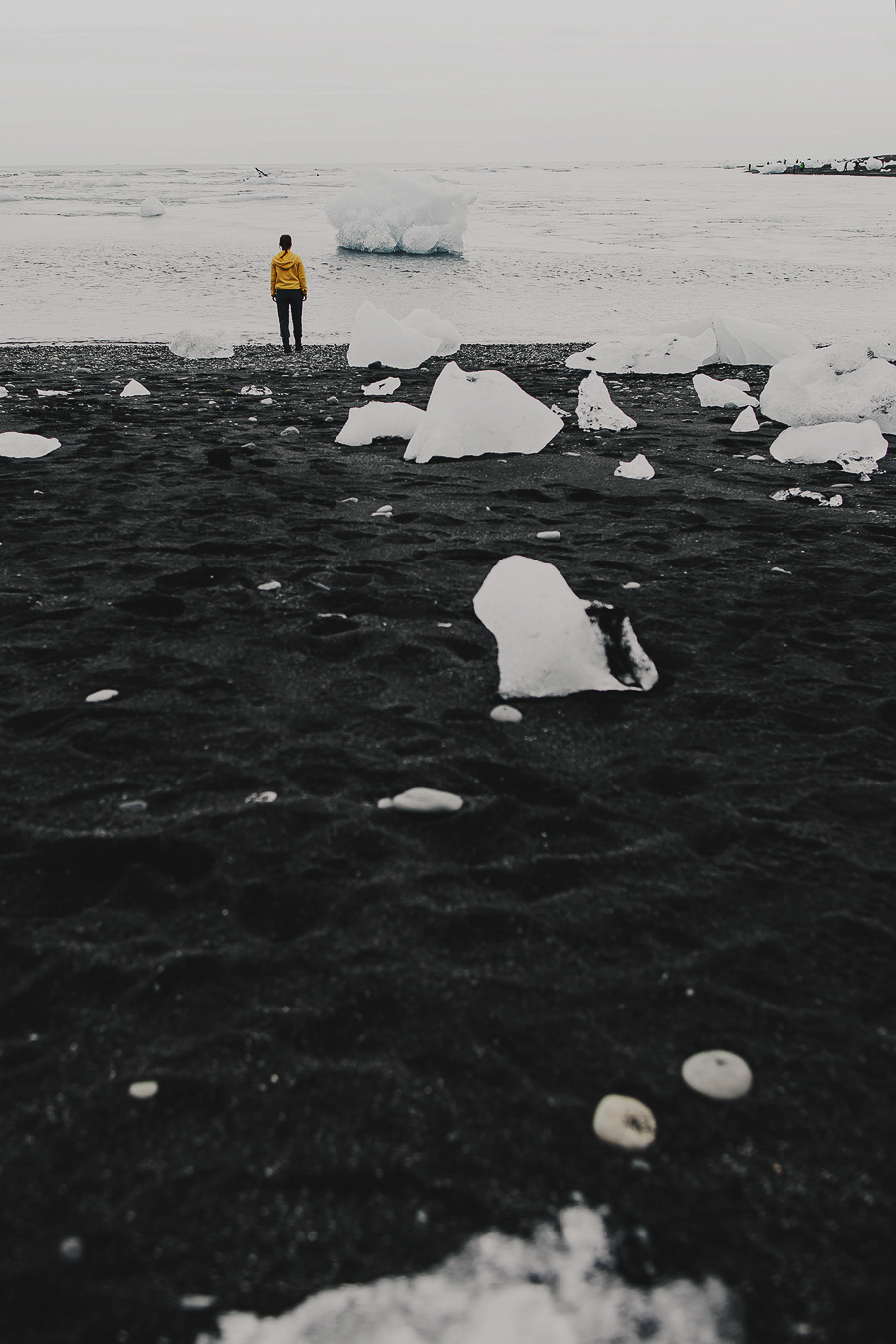 Girl in a yellow jacket standing by blocks of ice