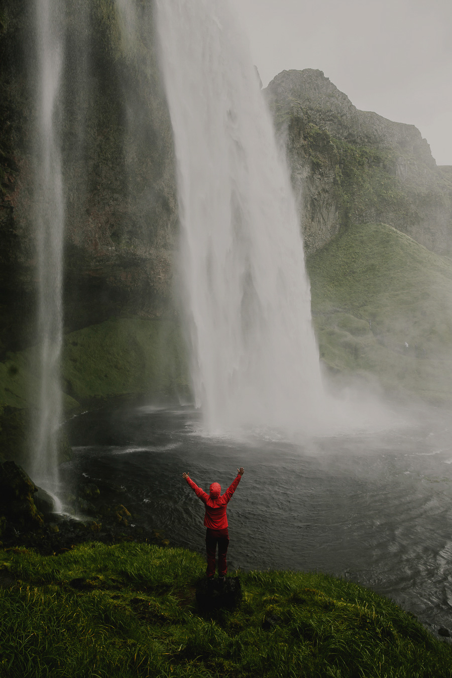 Girl standing in front of a waterfall