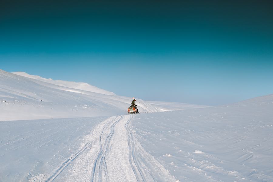 Guy driving on a snow mobile on Svalbard
