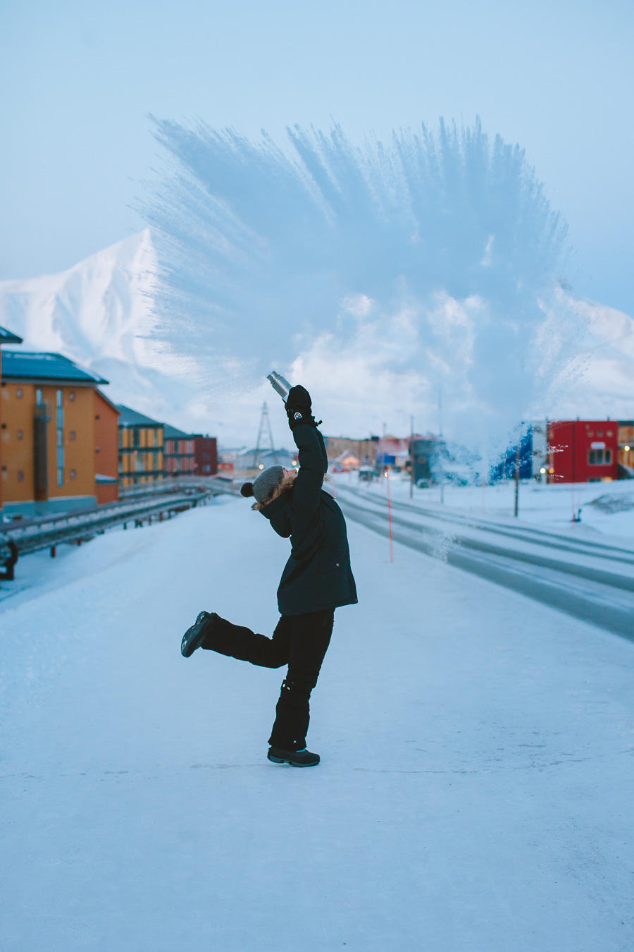 Girl throwing boiling water in ice cold air