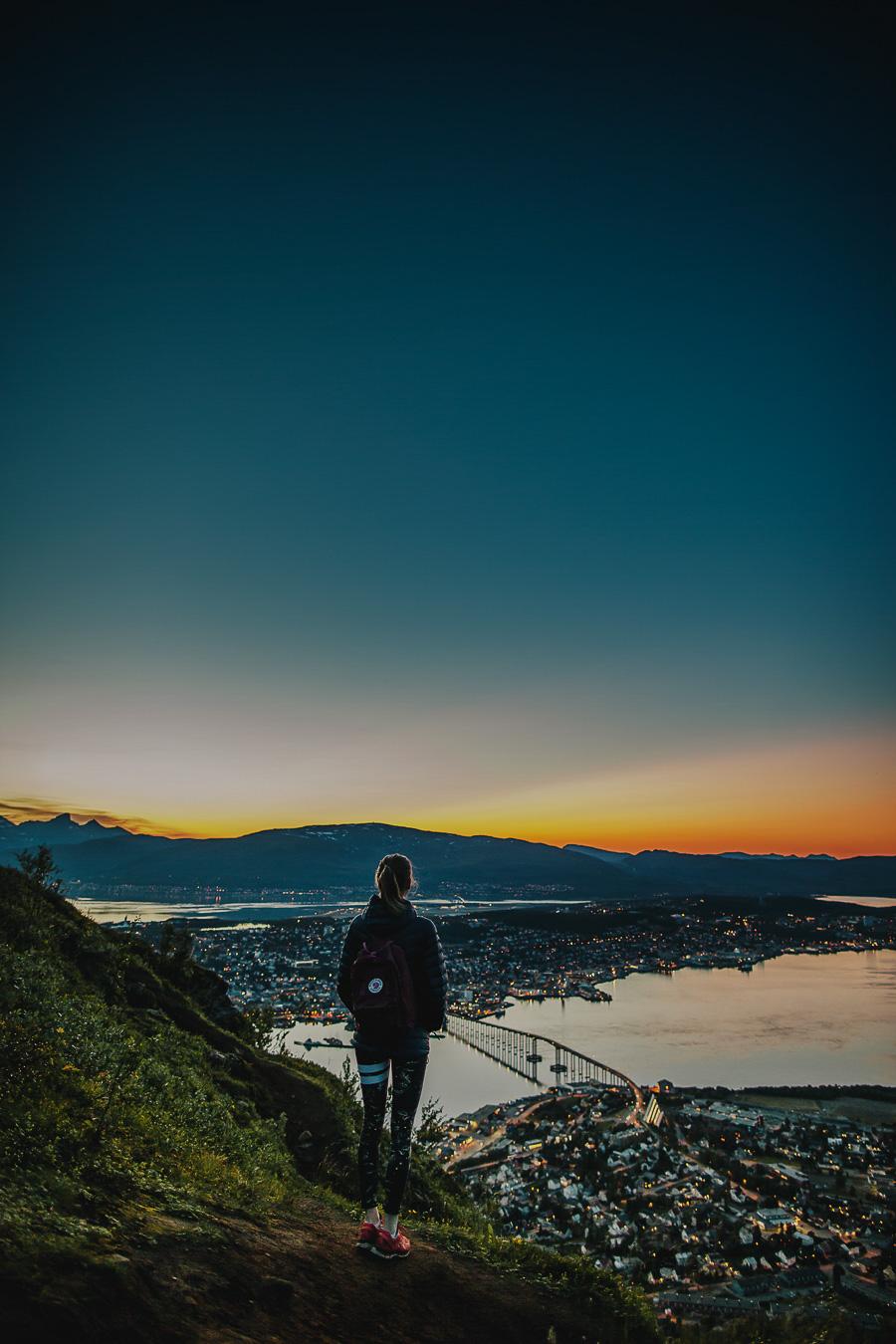 Girl looking at Tromsø at sunset
