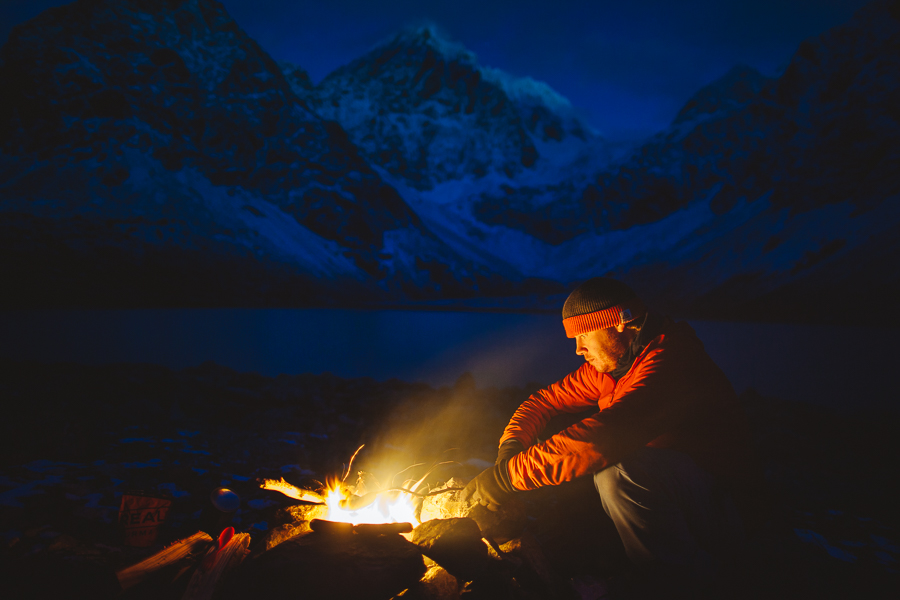 Man sitting by the fire outside by the mountains