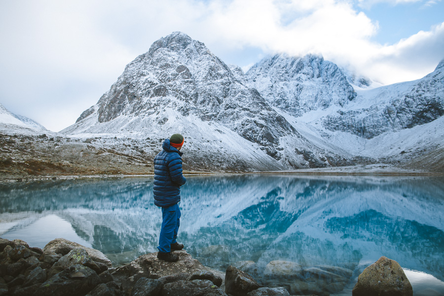 Man looking at the mountains mirrored in the glacier lake
