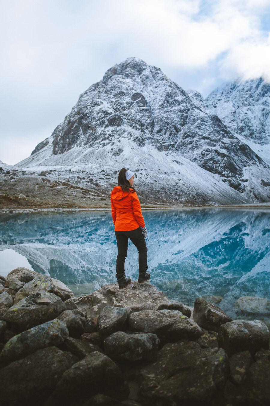 Girl in an orange jacket watching a mirrored lake