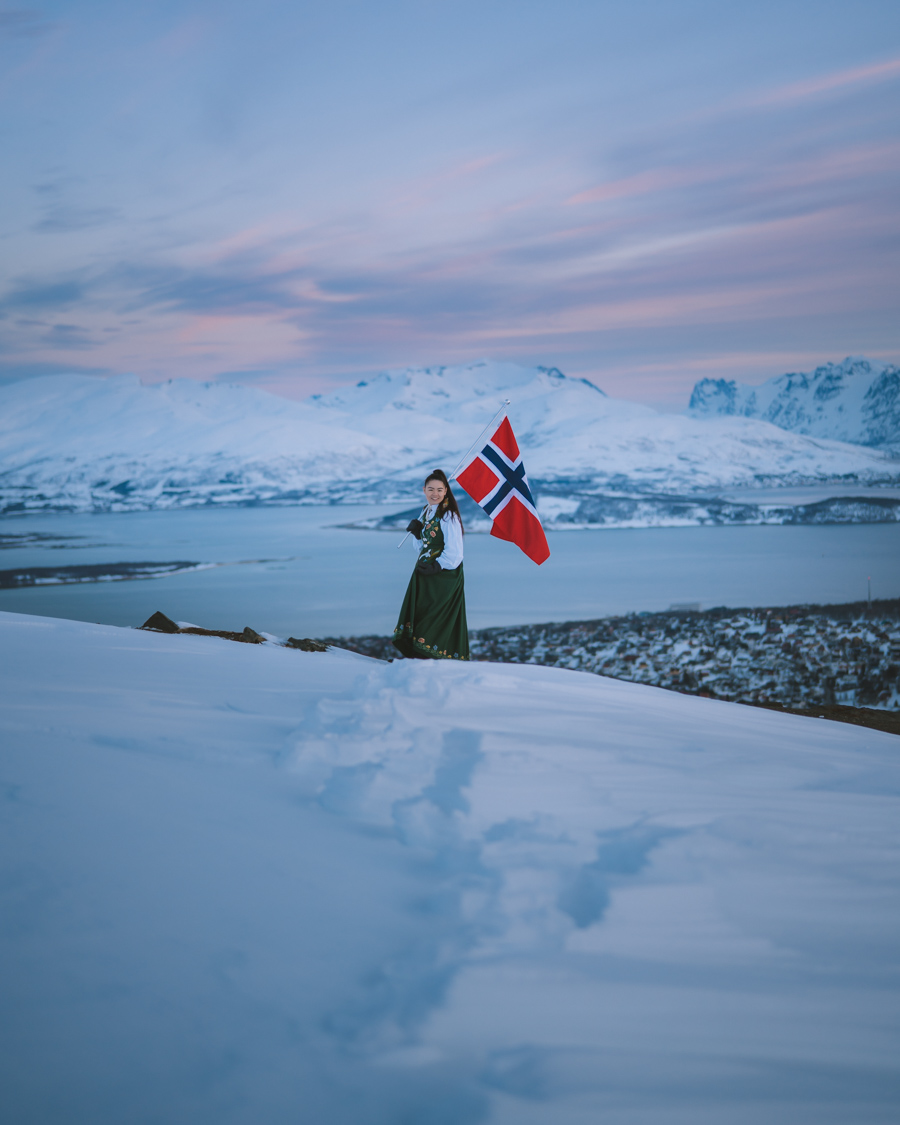 Girl in bunad waving the Norwegian flag