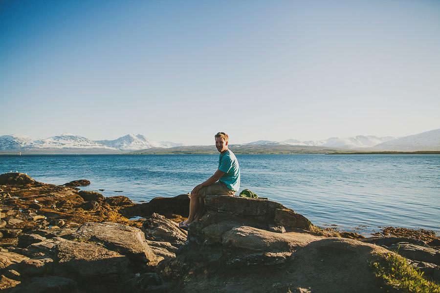 Boy sitting on a rock by the ocean