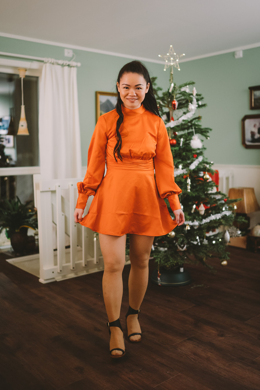 Girl wearing a orange dress in front of a christmas tree