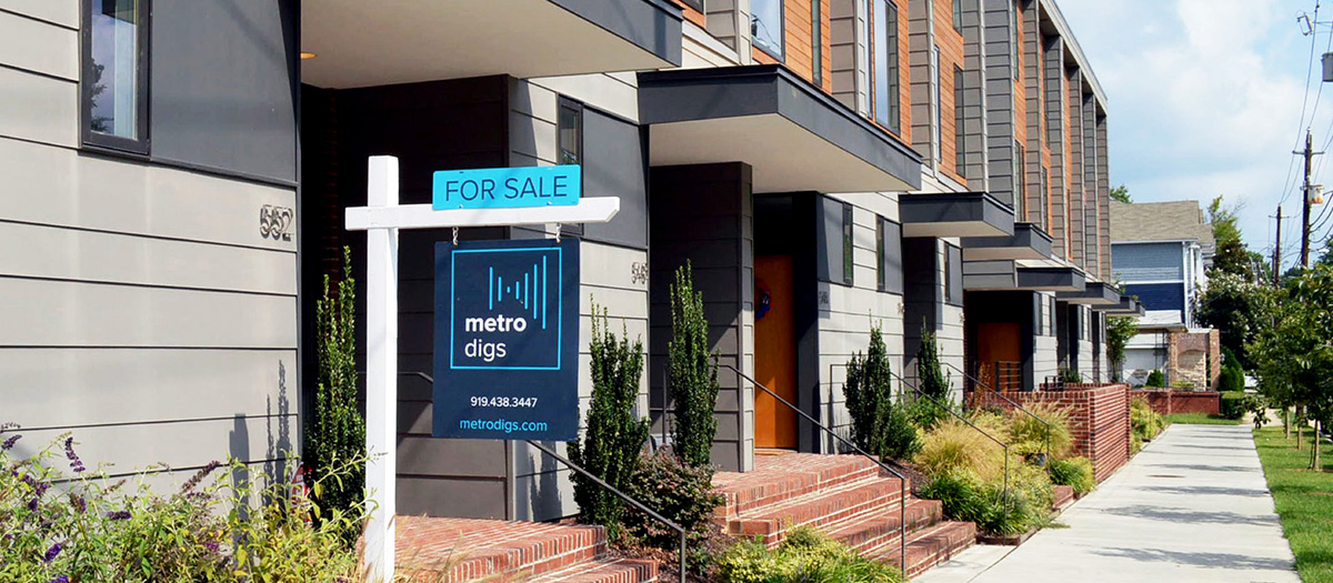 A row of modern townhomes with a Metro Digs for sale sign.