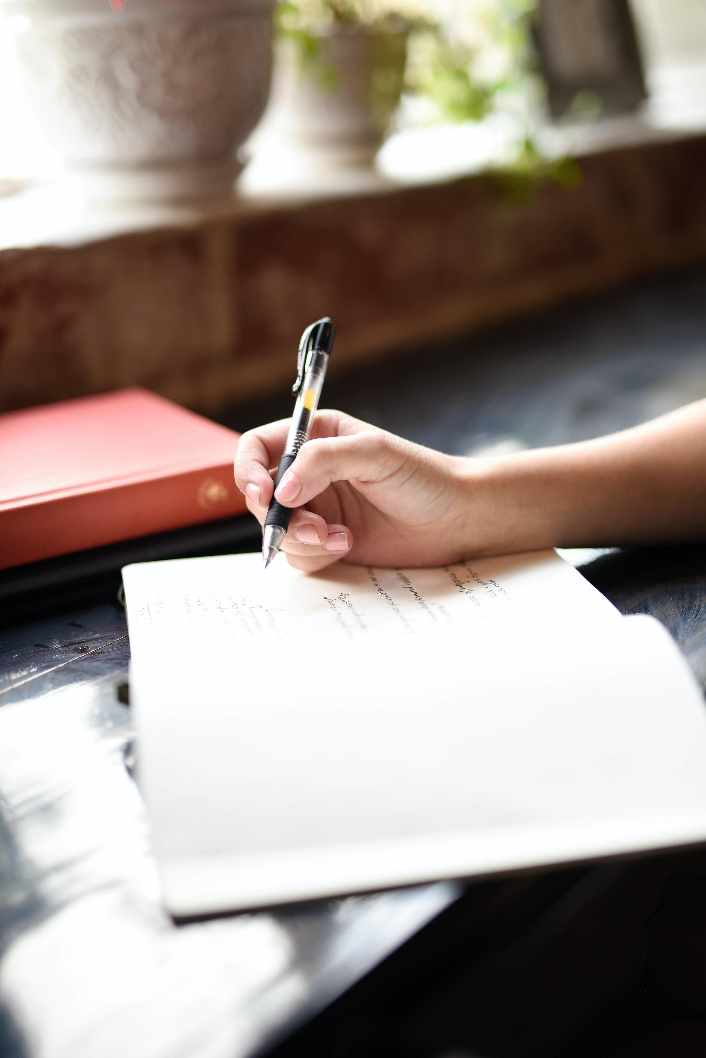 image cahier ouvert main qui écrit