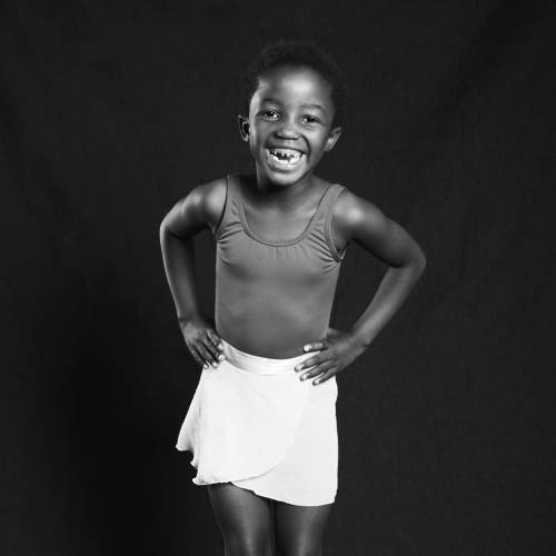 A black and white picture of Thandekile, smiling with her hands on her hips
