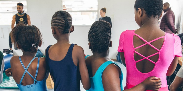 A group of Move For Two's dancers in brightly coloured leotards facing away from the camera