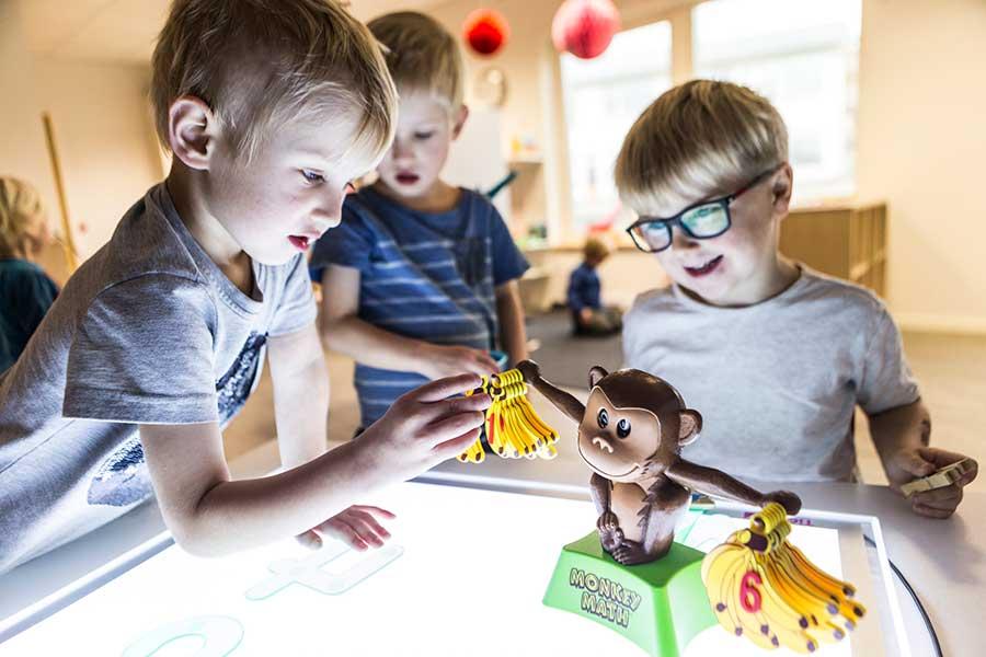 Tre killar på Thoren Framtid Förskola räknar leksaksbananer som de hänger upp på en plast-apa som står på ett ljusbord