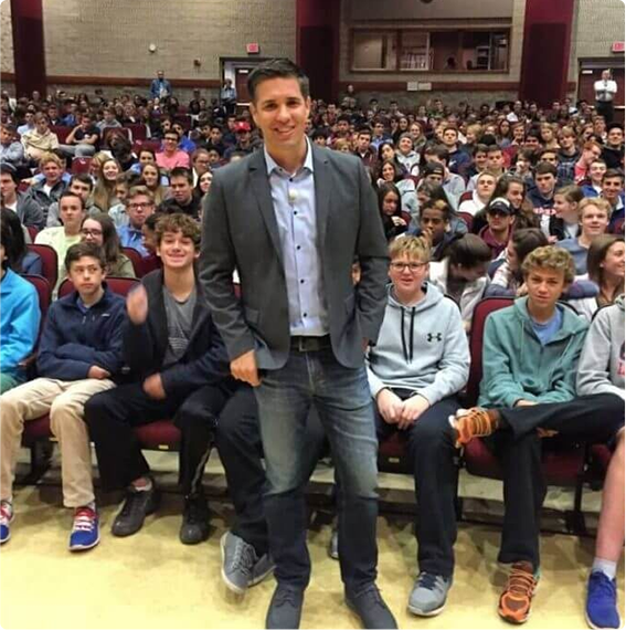 Josh Ochs standing in front of gymnasium of students at speech