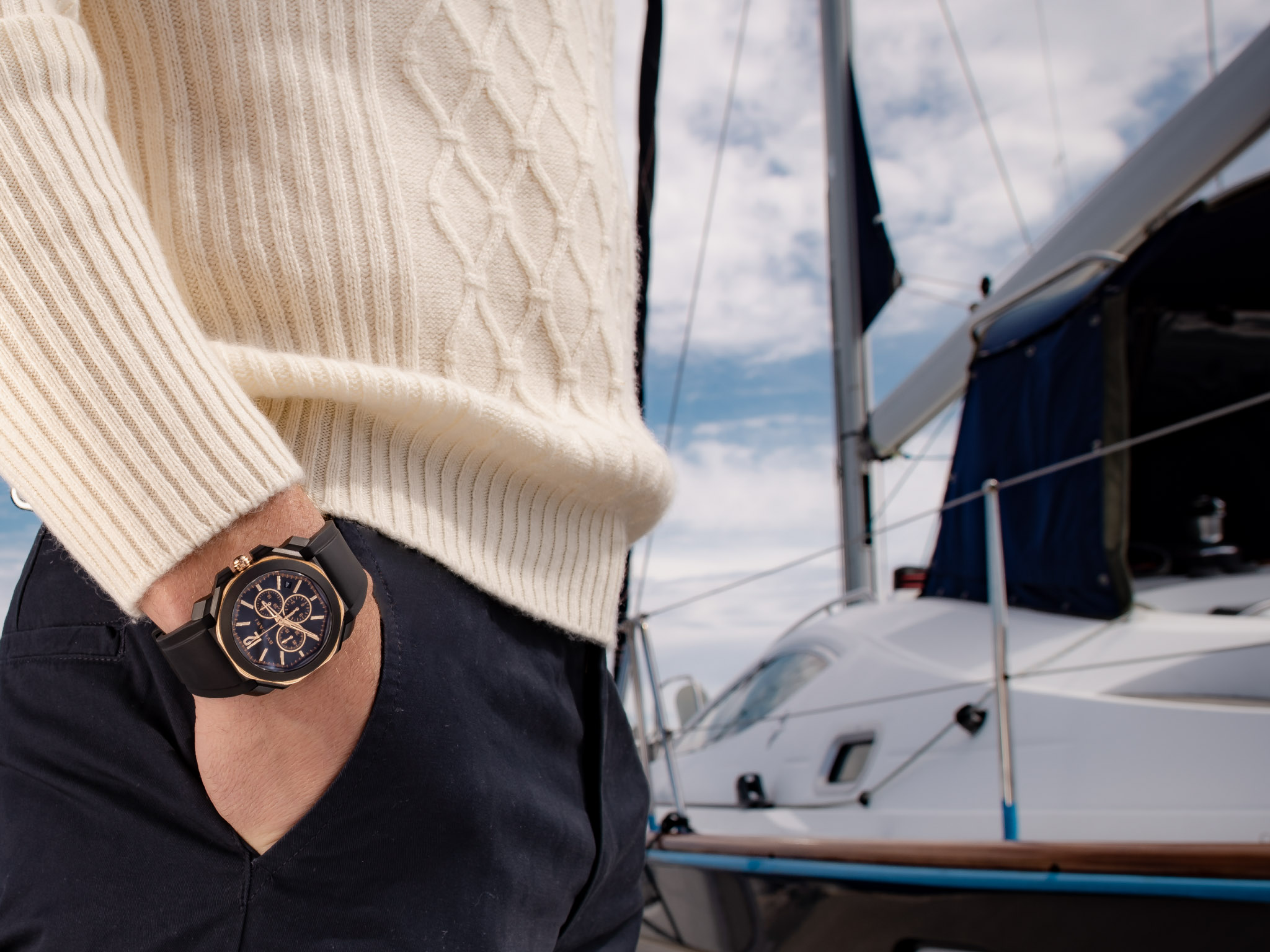 Content creator wearing luxury wrist watch against a yacht