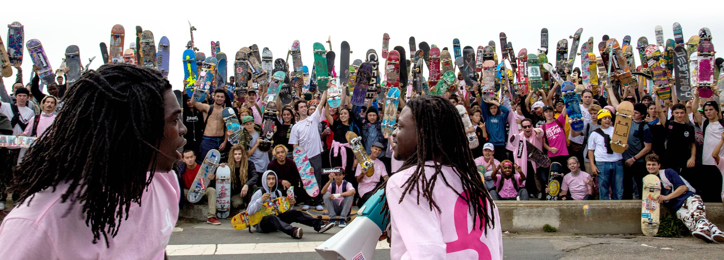 A group photo of skateboarders holding their boards in the air at the end of the 2017 Pushing For Pink event.