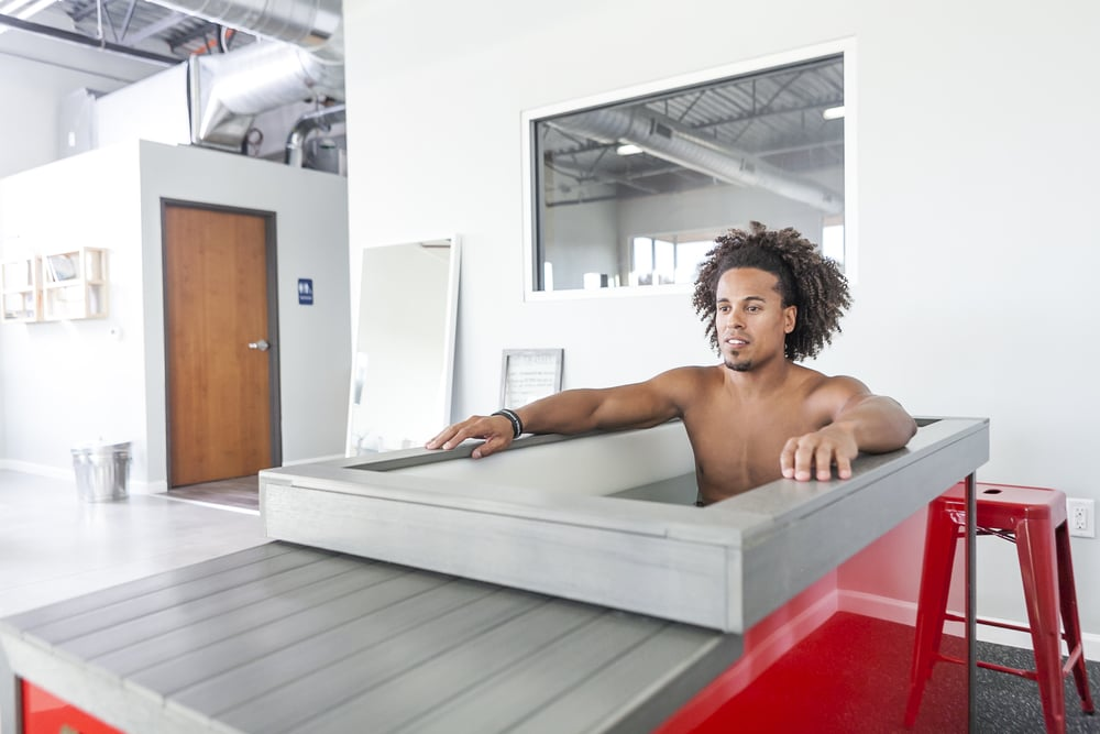 Man sitting in the cold tub at the Athletic Outcomes recovery lounge