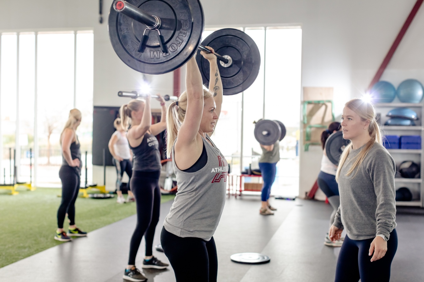 Coach Kat teaching women a barbell press during athletic outcomes women strength small group training class.