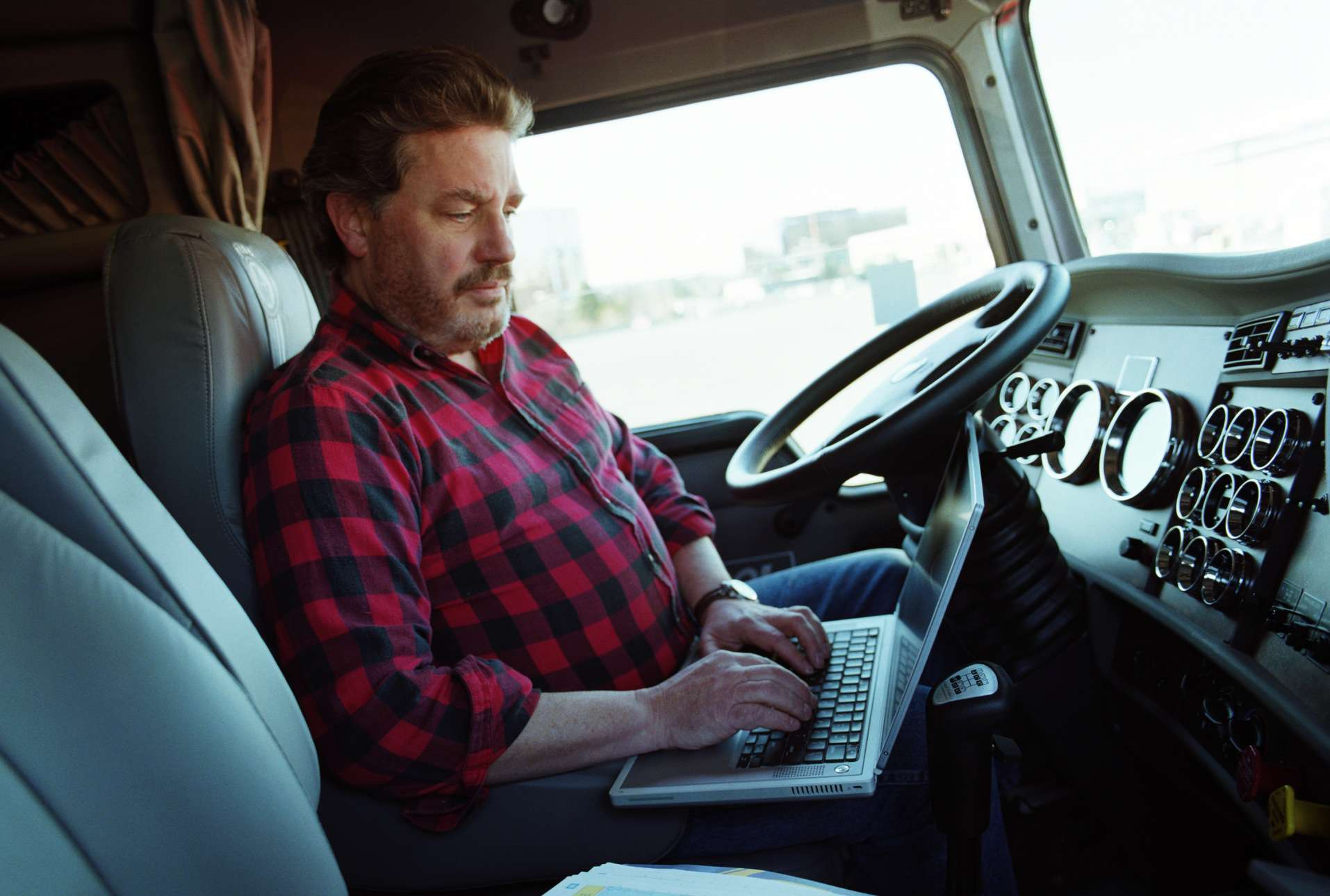 man in truck using computer