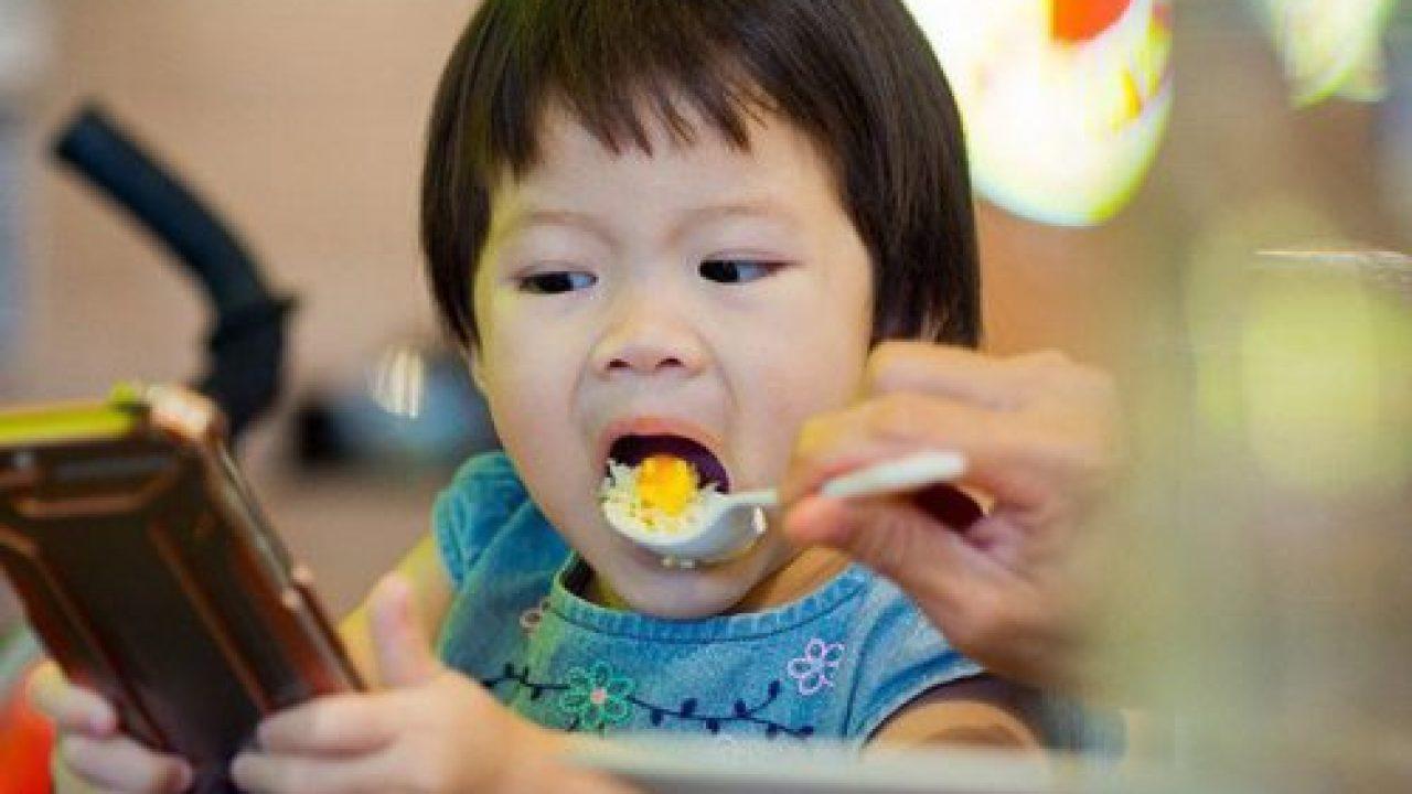 Cha mẹ không nên cho trẻ vừa ăn vừa xem điện thoại