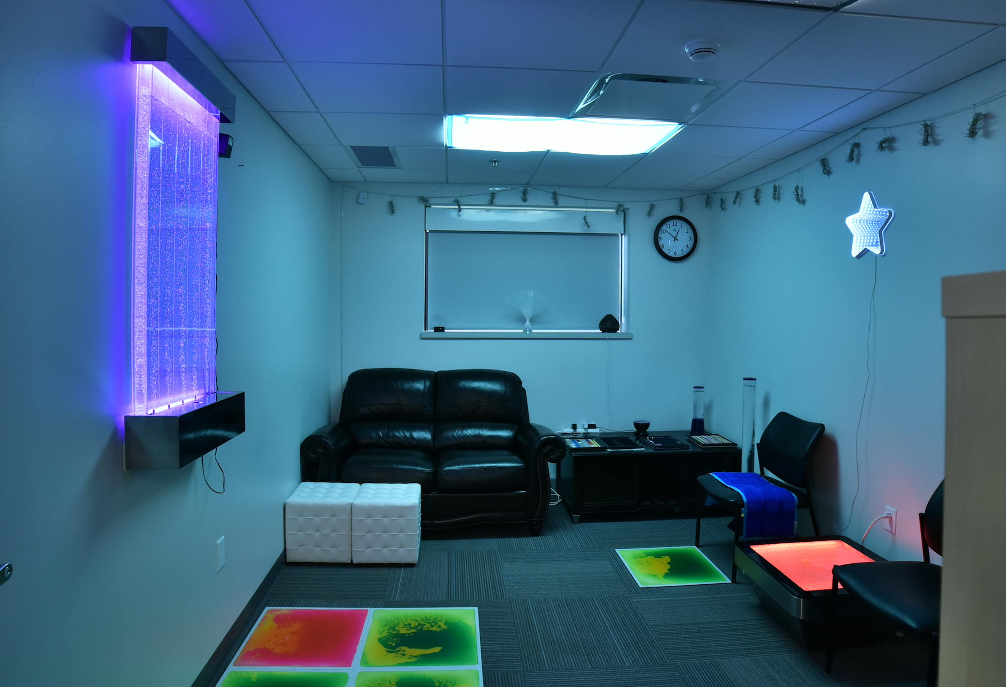 dimmed room with leather couch and other sensory items