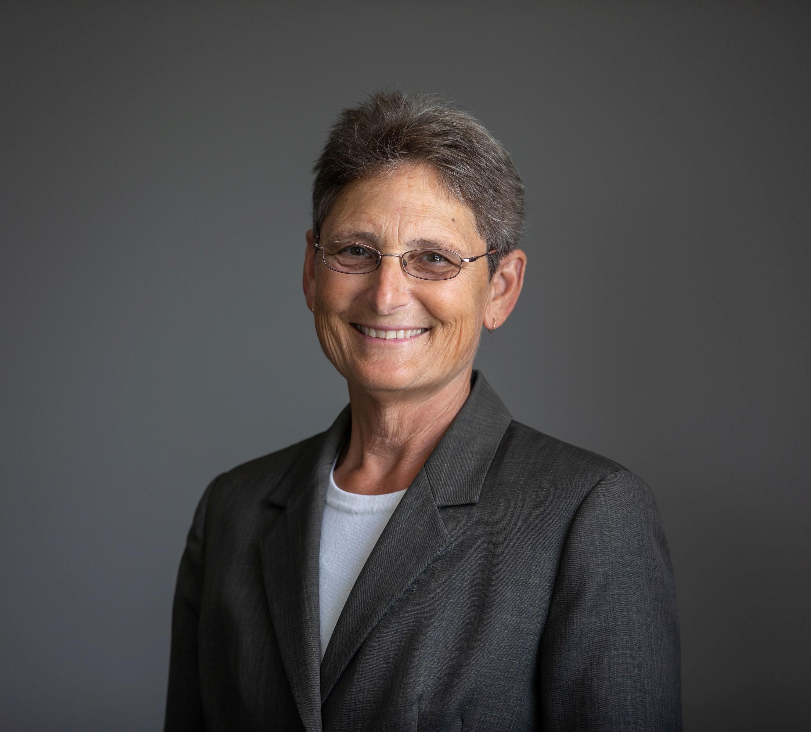 Smiling portrait of Ruth Siegfried against dark grey background