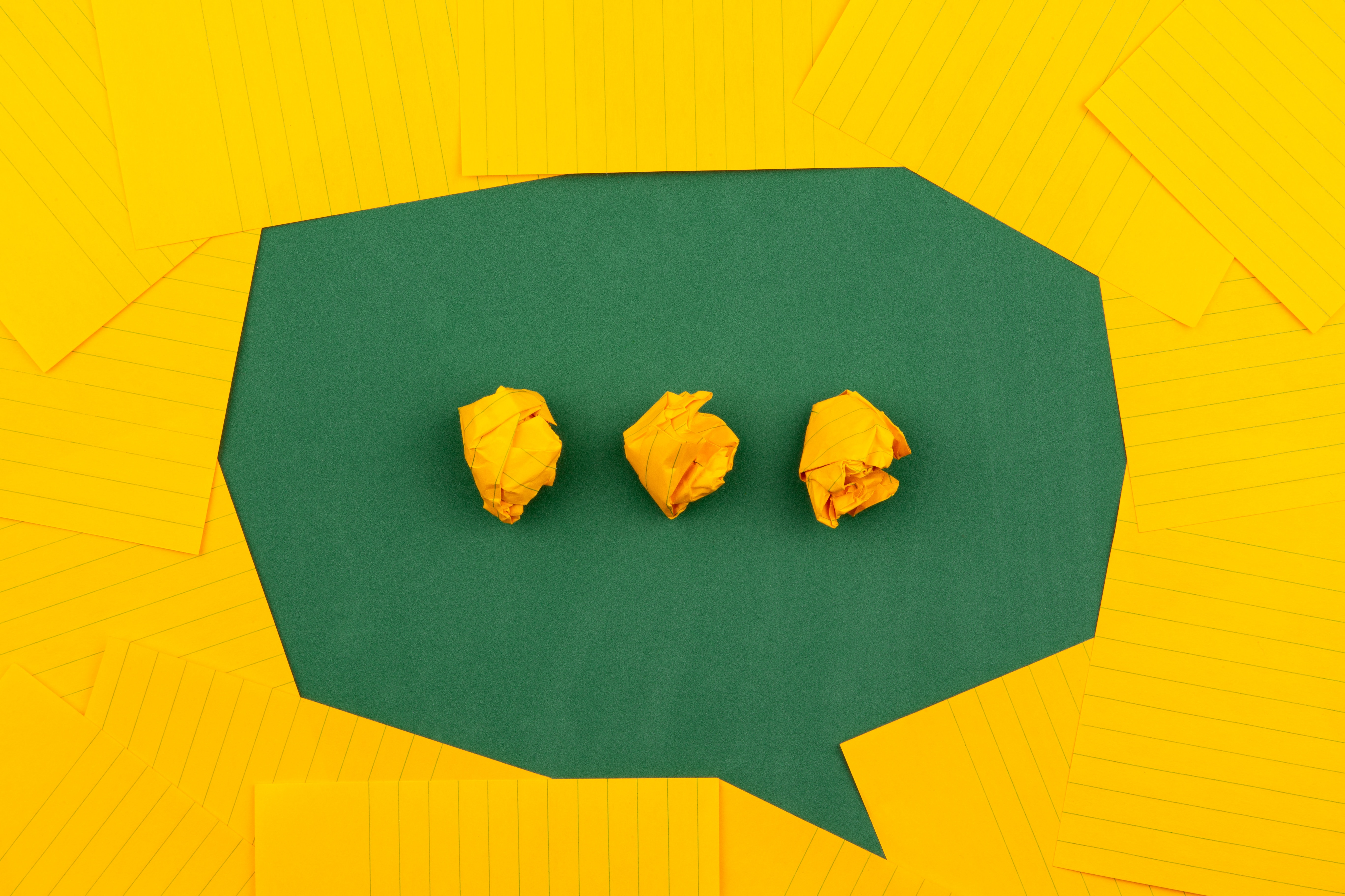 yellow paper surrounding three crumpled pieces of yellow paper in a row outlining a thought bubble