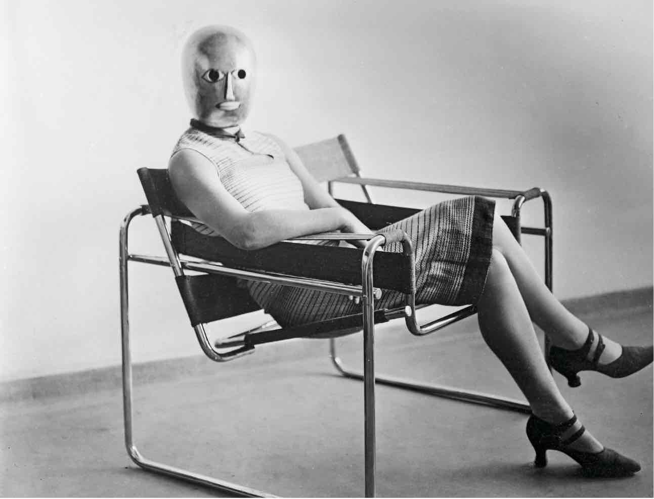 woman sitting on the tubular-steel chair wearing a mask became the most famous anonymous figure from the Bauhaus