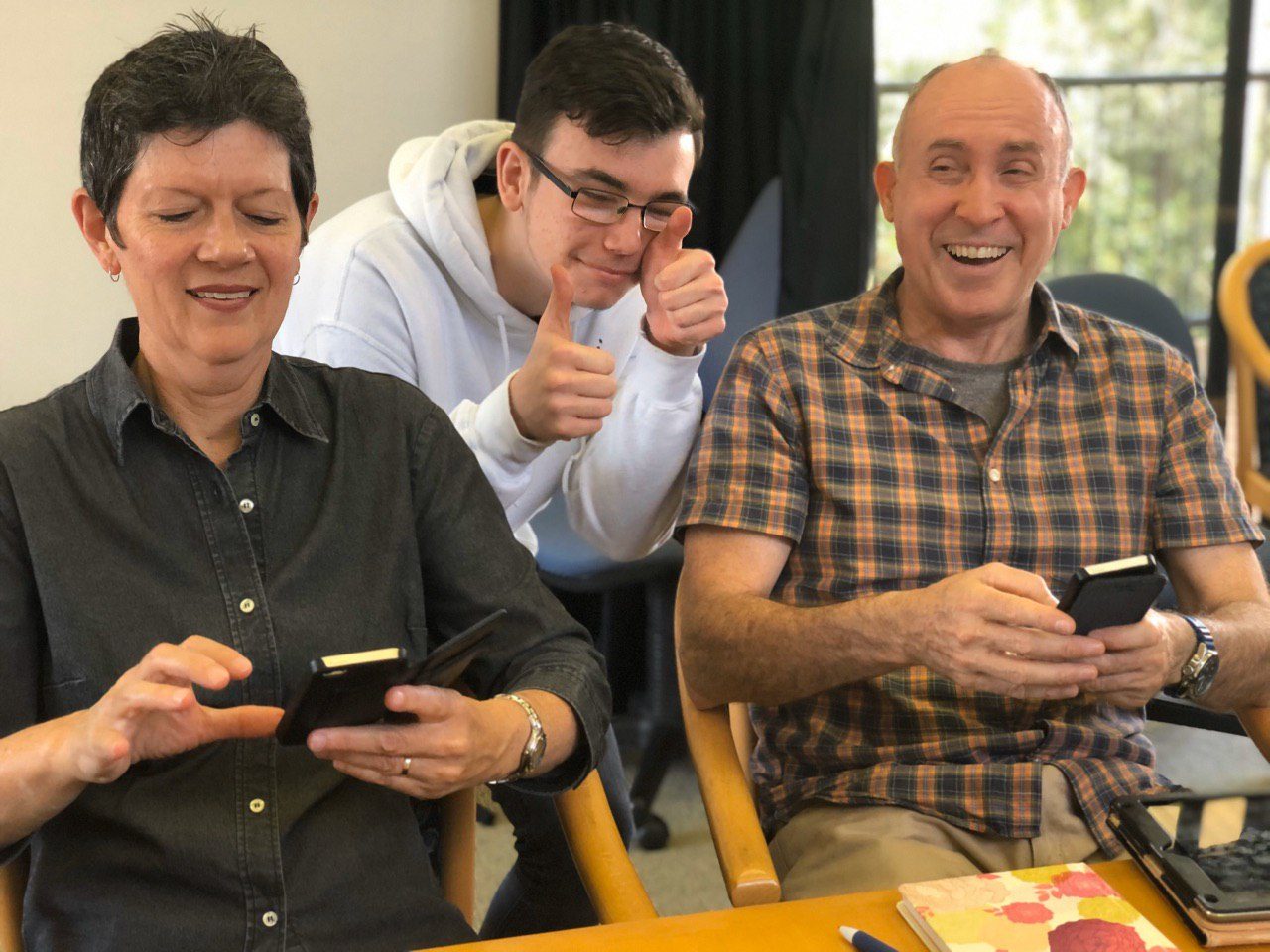 Two elderly people on phones and a youngster smiling with thumbs up displayed