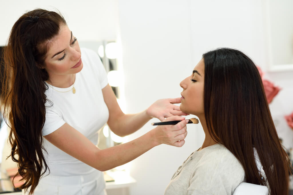 makeup artist applying makeup to clients face