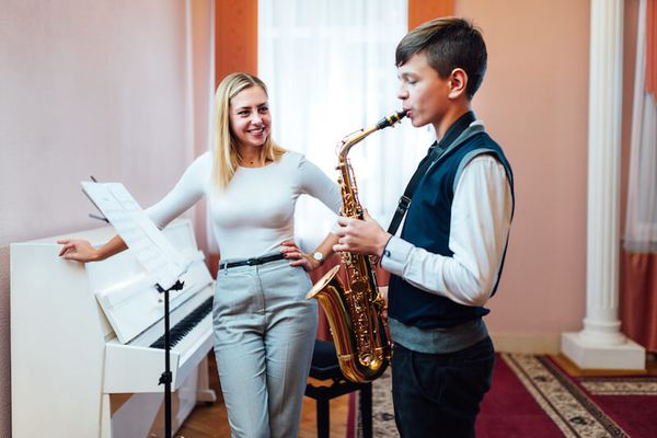 mobile music teacher with student playing saxophone