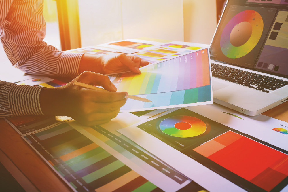 A designer points to colors printed on a sheet of paper. He is surrounded by color samples and a color wheel on a laptop.