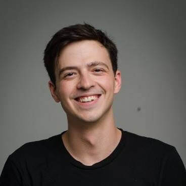 Profile on a young man with a black t-shirt on smiling and standing in front of grey background