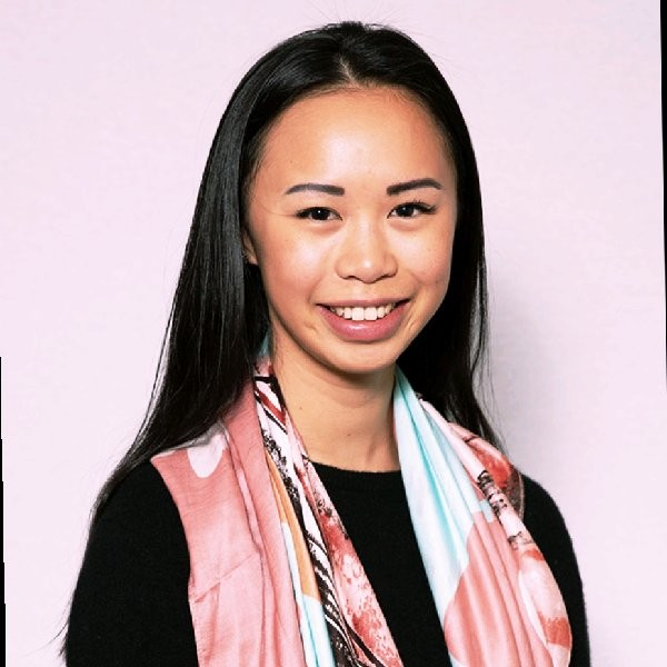 Profile of a young woman smiling with a scarf  and black t-shirt on standing in front of a pink back ground