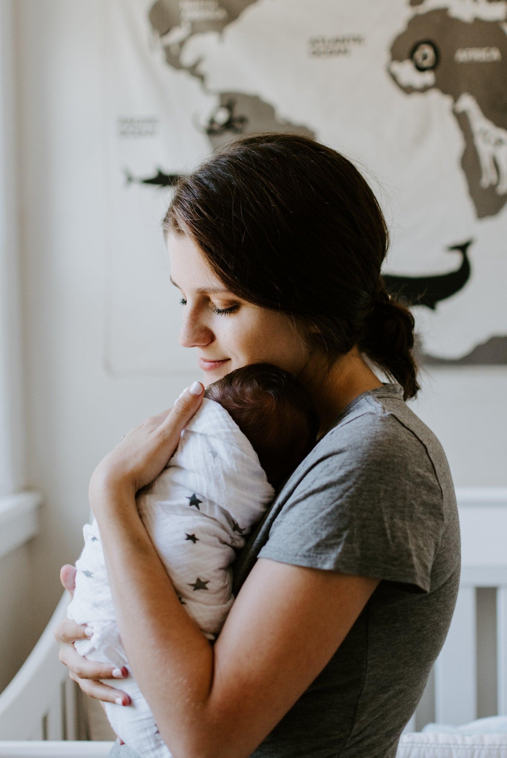 Image of loving mom putting baby down to sleep.