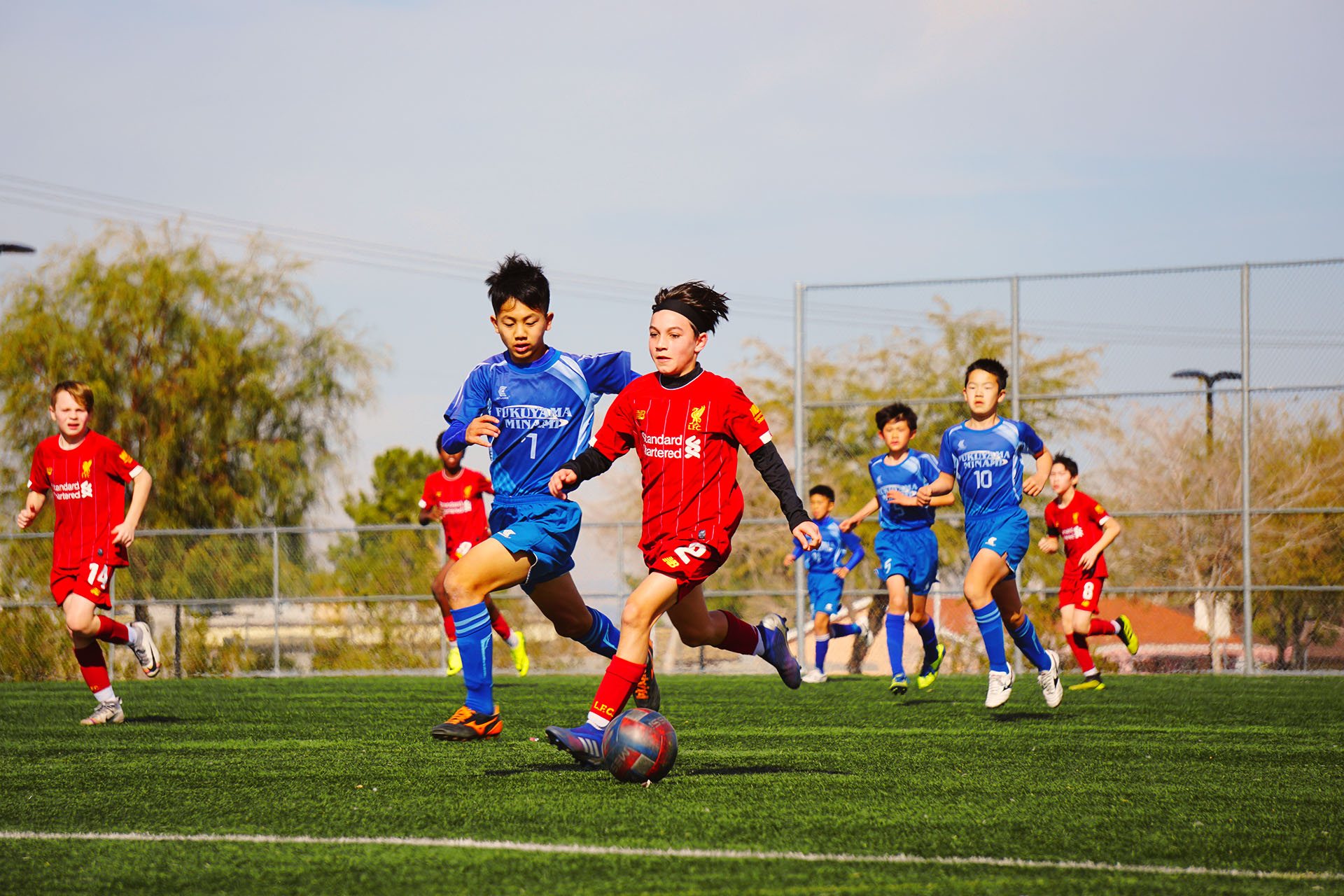 Kids from teams Fukuyama Minami and Liverpool FC compete for the ball during a football match in BA Cup 2020 in Las Vegas, Nevada