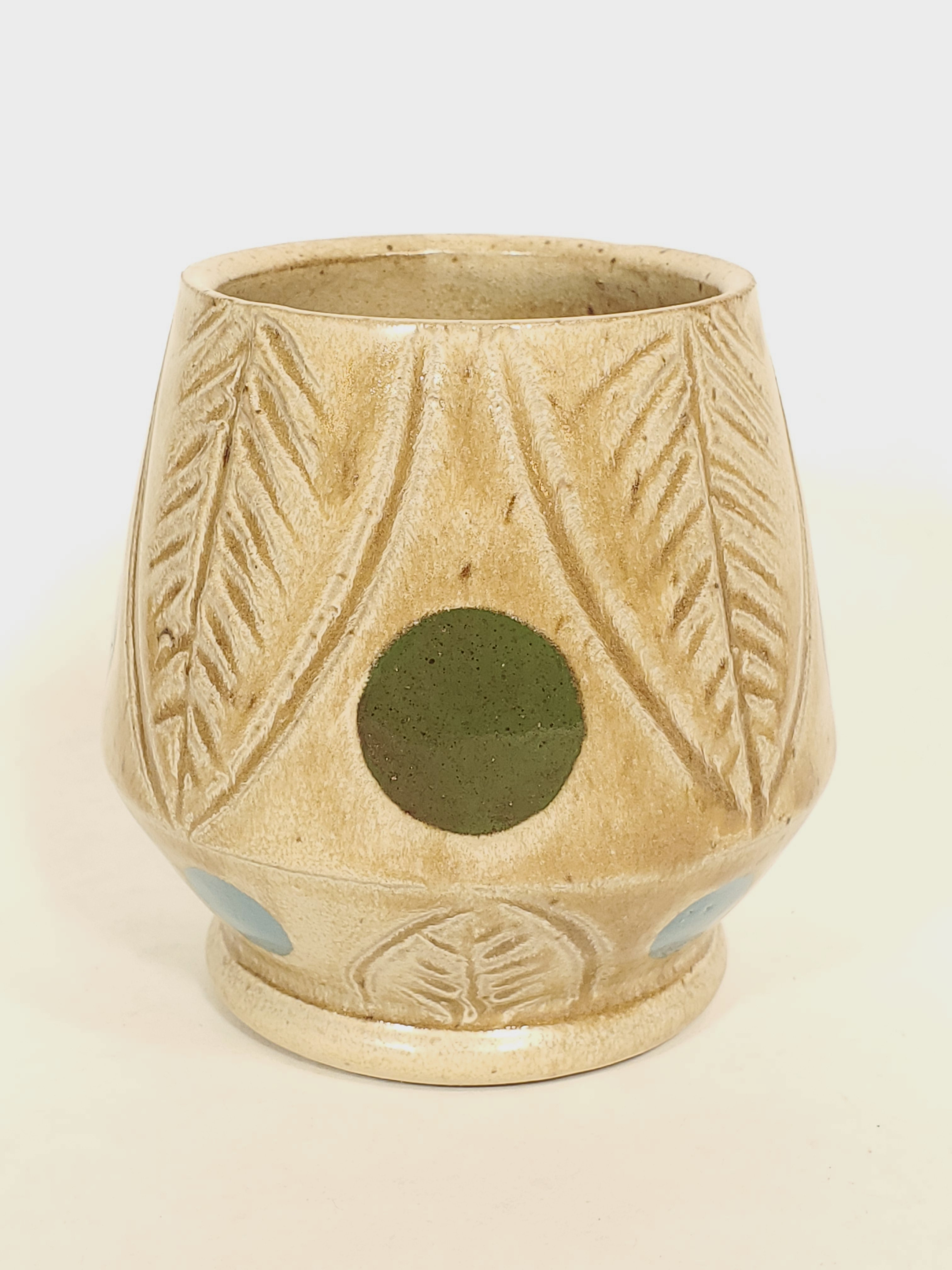 Small tan cup with leaves and dots