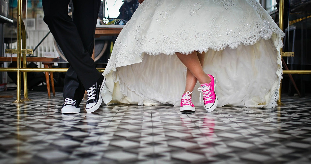 a bride and groom pose in converse sneakers