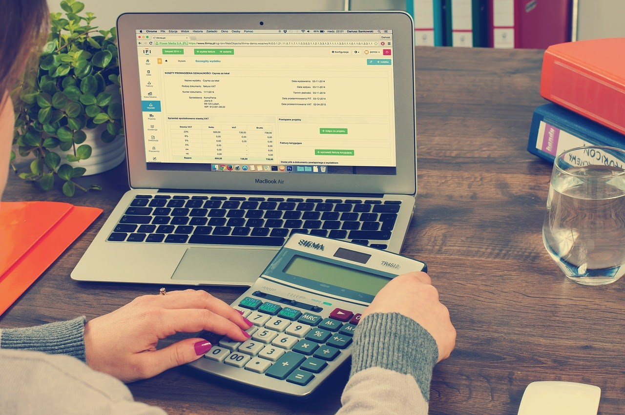 a woman calculates her budget using a calculator and online budgeting software