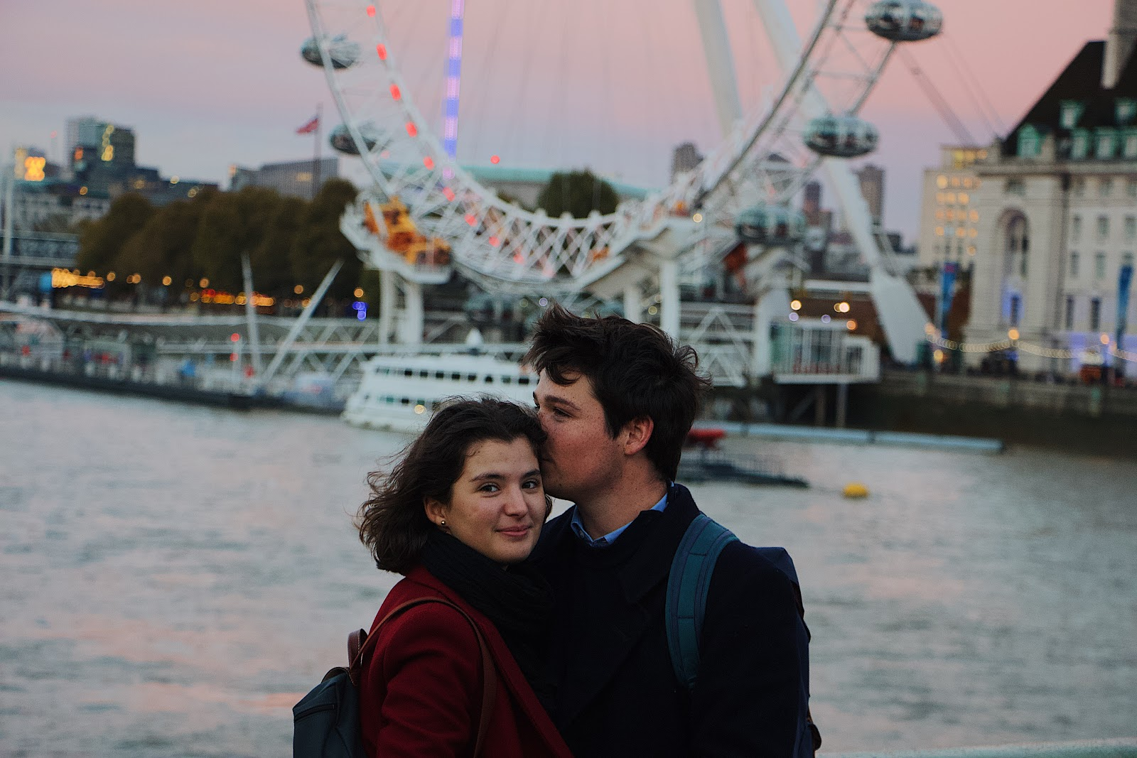 a man kisses a woman's head as they pose together on a pier