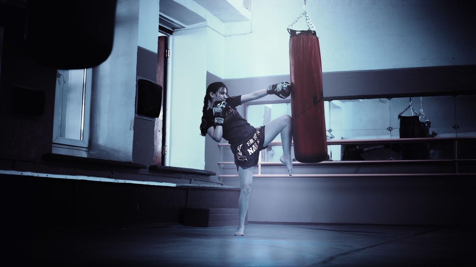 a woman hits a heavy bag during a fitness boxing class for adults