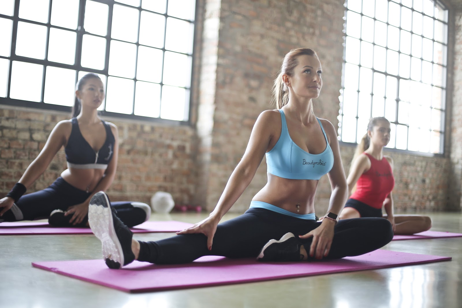 3 fit women stretch on yoga mats in a fitness class for adults
